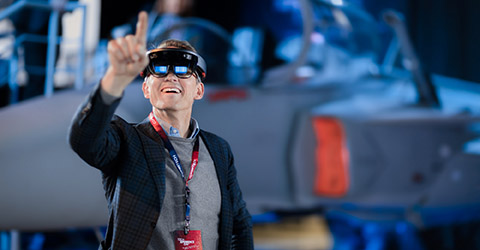 Visitor at Combitech Techxperience Day 2017 wearing Hololens goggles, pointing into the air
